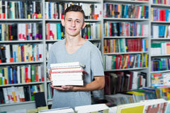 Portrait of glad teenager boy with book pile. In shop Royalty Free Stock Image