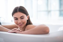 Optimistic girl leaning on side of bath stock photos