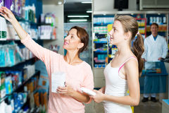 Portrait of glad woman with daughter teenager. Portrait of positive women with daughter teenager shopping healthcare products in drug store royalty free stock photos