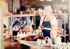 Portrait of glad woman pottery worker with ceramic crockery. Portrait of glad efficient women pottery worker with ceramic crockery in hands in studio royalty free stock images