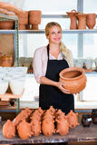 Portrait of glad woman pottery worker with ceramic crockery. Portrait of glad smiling  woman pottery worker with ceramic crockery in hands in studio Stock Photo