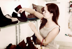 Portrait of glad woman selecting loafers. In footgear center Royalty Free Stock Images