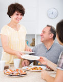 Portrait of glad woman serving dishes for lunch. Portrait of glad women serving dishes for family lunch at home Royalty Free Stock Photography