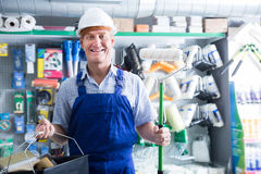 Portrait of glad workman choosing soft roller. Portrait of glad workman in uniform choosing soft roller for painting in housewares hypermarket Royalty Free Stock Photo