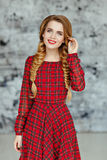 Portrait of a glamorous beautiful smiling girl with bright makeup in a red plaid dress and pigtails, in the studio on a gray back stock images