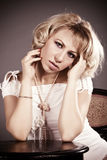 Portrait of glamorous blond woman. Portrait of beautiful young blond woman wearing white designer dress and pearl necklace Stock Image