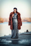 Portrait of the glamorous brunette lady in expensive fur coat watching river. Royalty Free Stock Photo