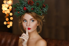 Portrait of a glamorous girl with red lips with a wreath of Christmas trees on his head. royalty free stock image