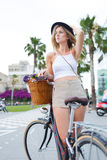 Portrait of a glamorous tourist woman enjoying summer vacation riding on retro bicycle with a basket of flowers Royalty Free Stock Photography