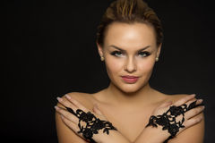 Portrait of a glamorous woman. Wearing elegant black lace gloves with her hands crossed over her bare shoulders with an enigmatic smile Stock Photo