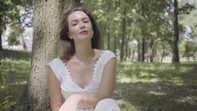 Portrait glamorous young girl with long brunette hair wearing a long white summer fashion dress sitting under a tree in stock footage