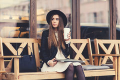 Portrait of a glamorous young woman holding on her knees portable laptop computer while sitting on a wooden bench Royalty Free Stock Photos