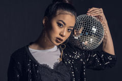 Portrait of glamour asian girl posing with disco ball and looking at camera Stock Image