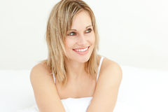 Portrait of a glowing woman in the morning. Portrait of a glowing woman sitting oon her bed in the morning Stock Photography