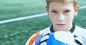 Portrait of teenage goal keeper holding ball on school soccer pitch. Portrait of goal keeper holding ball on school soccer pitch Royalty Free Stock Images