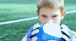 Portrait of teenage goal keeper holding ball on school soccer pitch. Portrait of goal keeper holding ball on school soccer pitch stock images