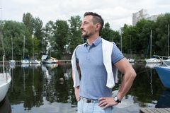 Portrait of goatee man in marina with boats. Successful man on river beach with boats and forest background stock photo