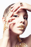 Portrait of a golden girl. Studio photo of a young woman in gold leaf Royalty Free Stock Images