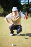 Portrait of golfer crouching and looking his ball Royalty Free Stock Photos