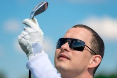 Portrait of a golfer looking at his golf club. Close up stock photo