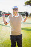 Portrait of golfer smiling and holding his golf club. On a field Royalty Free Stock Image
