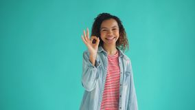 Portrait of good-looking African American lady showing OK gesture and laughing. Looking at camera. Millennials, satisfied people and happiness concept stock video