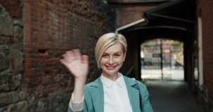 Portrait of good-looking elegant lady waving hand standing in the street stock footage