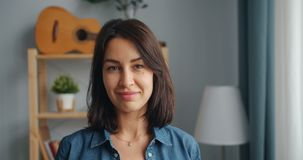 Portrait of pretty girl in casual clothing smiling looking at camera at home. Portrait of good-looking girl in casual clothing smiling looking at camera standing stock video