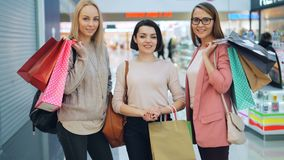 Portrait of good-looking girls wearing trendy clothing and accessories holding shopping bags in large shopping mall