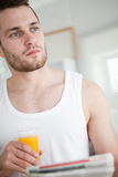 Portrait of a good looking man drinking orange juice while readi. Ng the news in his kitchen Royalty Free Stock Photography