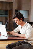 Portrait of a good looking man using a laptop. In a cafe stock image