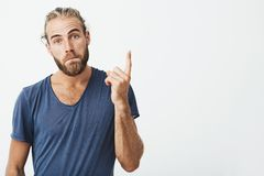 Portrait of good-looking manly guy with trendy hairstyle and beard looking at camera, pursuing lips and pointing up site Royalty Free Stock Photos