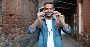 Portrait of good-looking middle Eastern man taking off sunglasses smiling. Standing outdoors in the street in city with hapy face. Youth and style concept stock video