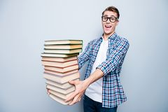 Portrait of good-looking, a-student, handsome reader high school. Teen in checkered shirt on light gray background hold a lot of books in hands ans make big royalty free stock images