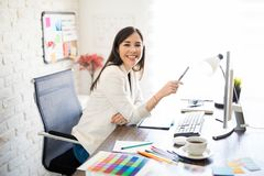 Woman graphic designer in her office. Portrait of a good looking woman graphic designer working at her desk and making an eye contact stock images