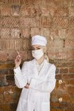 Portrait of a good looking young blond nurse with disposable syringe in her arms in a red brick background. Stock Images