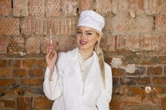 Portrait of a good looking young blond nurse with disposable syringe in her arms in a red brick background. Royalty Free Stock Photo