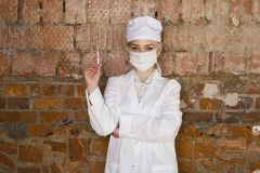 Portrait of a good looking young blond nurse with disposable syringe in her arms in a red brick background. Stock Photos