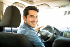 Good looking guy driving car. Portrait of good looking young hispanic man sitting in the driving seat of the car and looking back with a smiling face stock photo