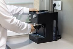 Man holding a coffee handle in a coffee machine on a table stock photos