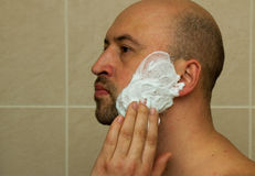 Portrait of a good looking young man putting shaving cream on his face and ready to shave his beard in the bathroom Royalty Free Stock Photo