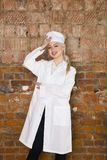 Portrait of a good looking young blond nurse with her arms crossed in a white background Stock Photography