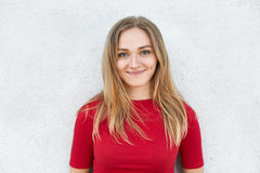 Portrait of good-looking young woman with straight blonde hair, warm green eyes and dimples on her cheeks wearing red T-shirt isol Stock Photos