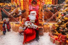 Sack with gifts. Portrait of good old Santa Claus holding a sack with gifts on the porch of his decorated house. House of Santa Claus. Christmas and New Year stock image