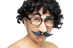 Goofy man winking. Portrait of a goofy man with curly wig and comedy eyeglasses over white background Stock Photo