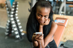 Portrait of gorgeous black lady with luxury long hair texting on her smartphone in the gym Stock Photography