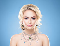 Portrait of gorgeous blond wearing luxury necklace with a gem ov. Beautiful blond girl with luxury golden necklace over blue background Royalty Free Stock Photos