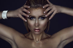 Portrait of gorgeous blond woman with wet hair and glittering artistic make up holding her hands close to the face Royalty Free Stock Photography