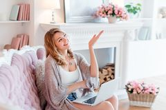 Portrait of gorgeous blonde woman with laptop working at home. Beautiful freelancer female talking in a video conference royalty free stock photography