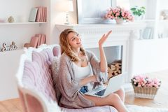 Portrait of gorgeous blonde woman with laptop working at home showing something. Beautiful freelancer female talking in stock photos